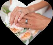 Zwei Hände mit Eheringen über dem Brautstrauß
